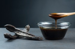 carob molasses in glass bowl and in wooden spoon and carob pods on rustic background, locust bean healthy food, Ceratonia siliqua ( harnup )