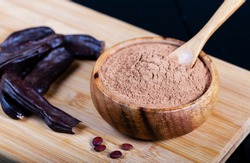 Carob pods and carob powder over wooden background