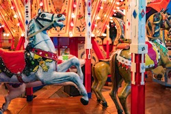 Carousels. Wooden horses spin around the post. Joy for children. Children's entertainment. The bright carousels are empty. Carousels are waiting for kids. Riding on wooden horses.