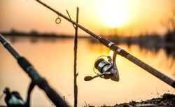 carp fishing rod isolated on lake. feeder fishing reel close up.