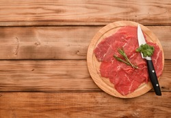Carpaccio dish of thinly sliced pieces (slices) raw beef tenderloin