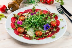 carpaccio from meat with vegetables, beef carpaccio with micro-green pea sprouts