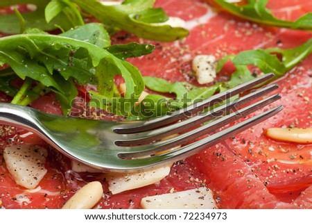 carpaccio on a plate with parmesan and pignolia