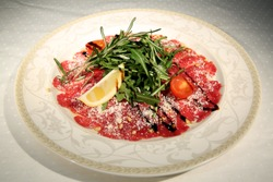 Carpaccio with lemon, tomato and arugula. Marbled beef carpaccio. Meat dish on a white plate. Healthy food restaurant menu. Cold appetizer. Source of protein. Organic healthy food.