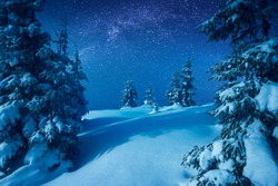 Carpathian mountain valley covered with fresh snow in a light of rising moon with. Fantastic milky way in a starry sky. Christmas winter night.