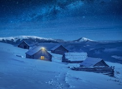 Carpathian mountain village illuminated by moon light with wooden houses on a hill covered with fresh snow. Fantastic milky way in a starry sky. Christmas winter night.