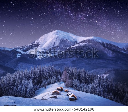 Carpathian mountain village in light of rising moon with wooden houses on a hill covered with fresh snow. Fantastic milky way in a starry sky. Christmas winter night. Foto stock ©