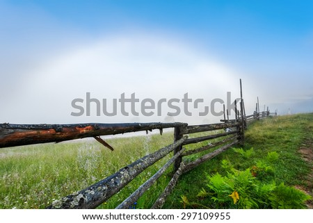 Carpathian Mountains. Overcast with a white rainbow, fence with cobwebs.