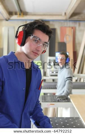Carpenter and apprentice in workshop - stock photo