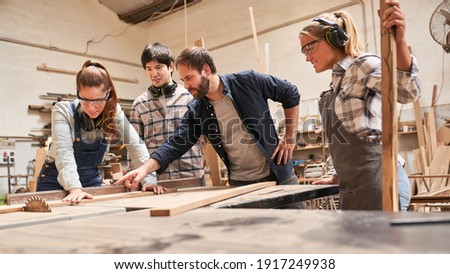 Carpenter apprentices with trainers at the circular saw in the carpentry workshop Photo stock ©
