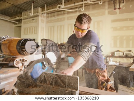 Carpenter at work on job using power tool