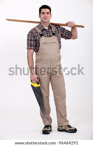 Carpenter carrying a plank of wood and a saw - stock photo