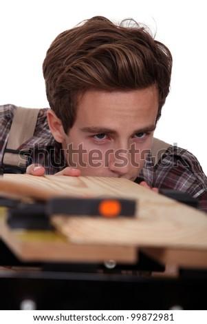 Carpenter checking plank of wood
