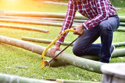 carpenter cutting bamboo for building bamboo hut