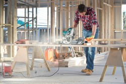 Carpenter cutting wood with circular power saw in building construction site interior