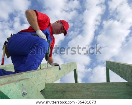 Carpenter drilling a hole in rafter framing beam - stock photo