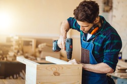 Carpenter drills a hole with an electrical drill