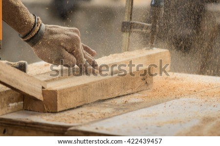 Carpenter engaged in processing wood at the sawmill. Working Site Rotary One Plank Plane Man Male Maker Motion Dust DIY Human Person Craft Safety Turning Electric Woodman Lumber Activity Skill Wood.