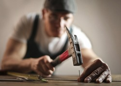 Carpenter hammering a nail