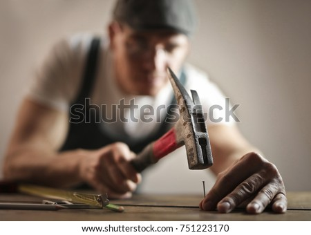 Carpenter hammering a nail\n