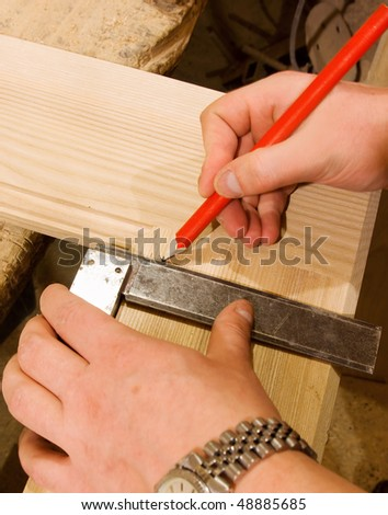 carpenter hand with square and pencil