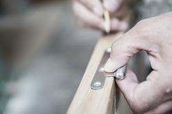 Carpenter hand working over door edge and hinge, shallow depth of field