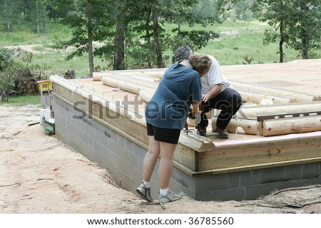 Carpenter helps mature woman home owner secure first log to her new log home.