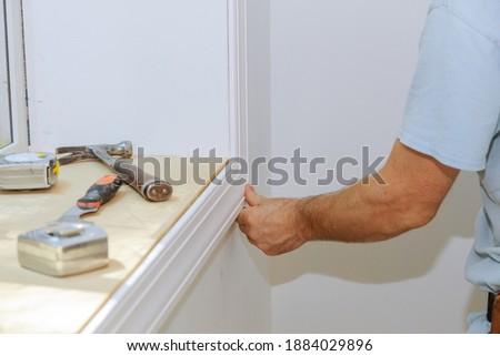 Carpenter installing to moldings on doors, nailing the framing trim Stock photo ©