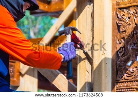 Carpenter is using chisel and hammer to groove vertical line. Close up hands of carpenter with chisel and hammer during grooving work.