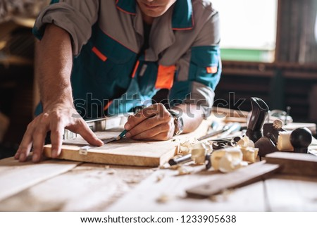 Carpenter, joiner at work in the workshop. Man at work on wood.