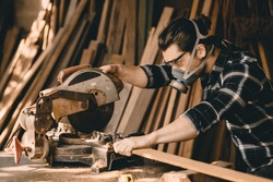 Carpenter man using Electric Wood Cutter machine with protection safety equipments in wood workshop
