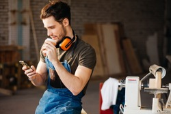 Carpenter Man using smart phone and holding cup of coffee in front of table with tools at workshop