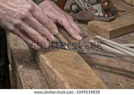 Carpenter marking measurements on piece of wooden board #1049018828