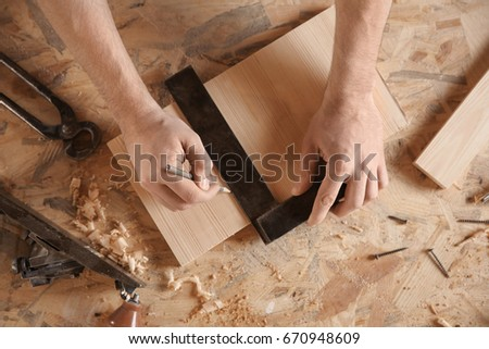 Carpenter marking wooden board in workshop #670948609