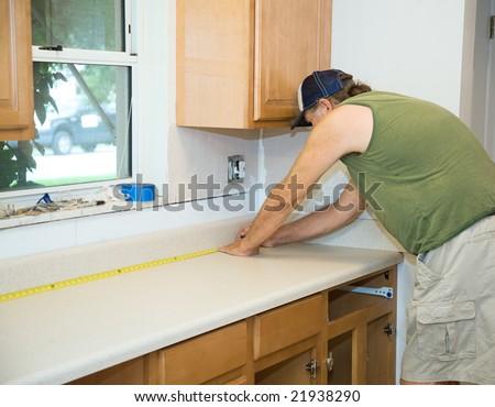Carpenter measuring laminate counter top during kitchen remodel.