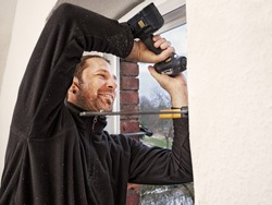 Carpenter Mounting a New Energy Efficient Window in Old Flat