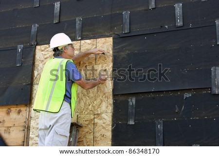 carpenter on a ladder doing construction to a house