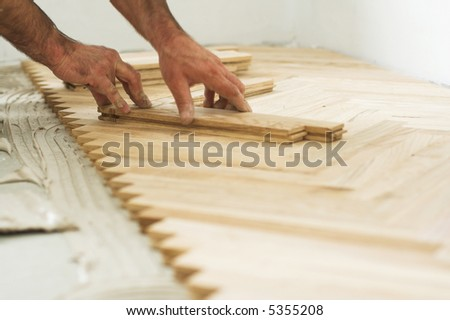 Carpenter on work putting wood parquet pieces. Home construction