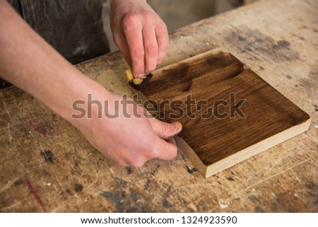 Carpenter painting wooden board in a wooden workshop. Profession, carpentry and woodwork concept. #1324923590