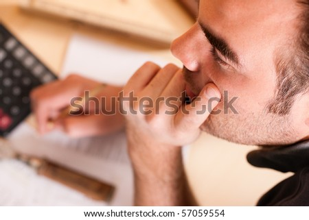 Carpenter planning his work - man thinking with set of tools, pencil, calculator and blueprint