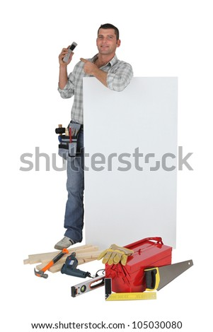 Carpenter pointing to mobile telephone whilst stood by blank poster