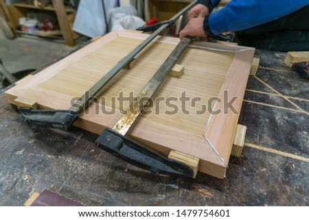 Carpenter presses used for manual assembly of a small table cover.