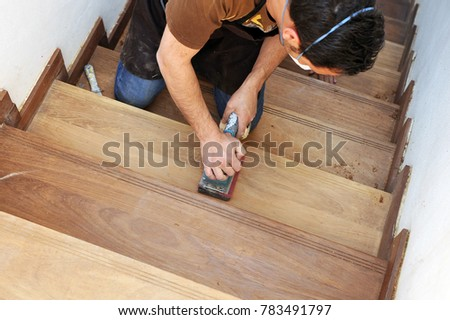 Carpenter sanding with electric sander polisher the steps of a teak wood staircase