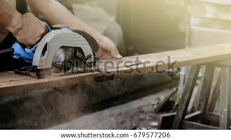 Carpenter using circular saw for cutting wooden boards with power tools.