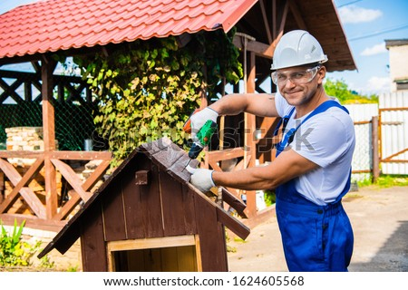 Carpenter using electric screwdriver. Man builds a roof of wooden planks of a small house. Building dog booth. Countryside house.
