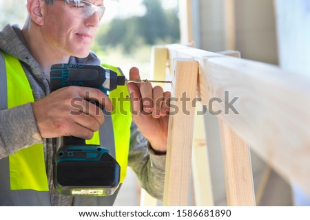 Carpenter using power drill to screw wood frame together on construction site interior