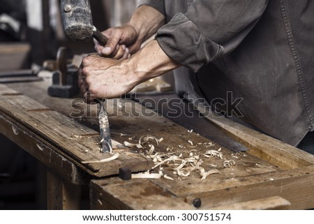 Carpenter with a hammer and chisel on the wooden workbench in carpentry