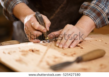 Carpenter with chisel in the hands on the workbench
