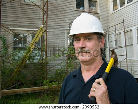 carpenter with hammer prepares to make repairs on house