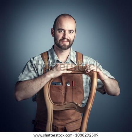 carpenter with unfinished chair, studio shot portrait